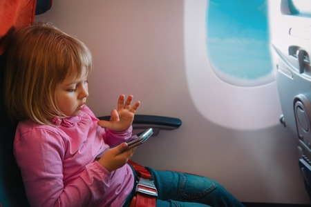 cute girl with mobile phone in flight Stock Photo