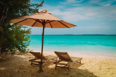 Two beach chairs on tropical vacation at sea Stock Photo