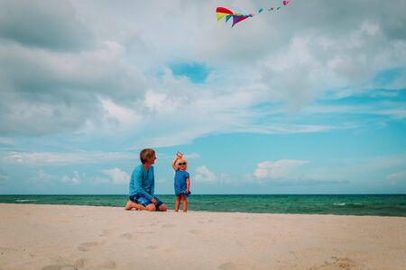 father and cute little daughter flying a kite at sky on beach