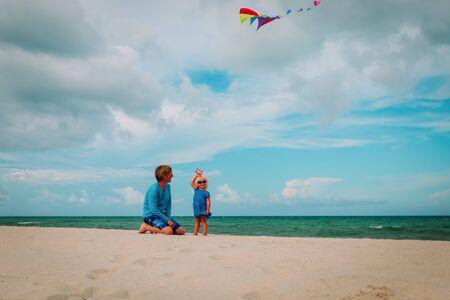 père et petite fille mignonne faisant voler un cerf-volant au ciel sur la plage