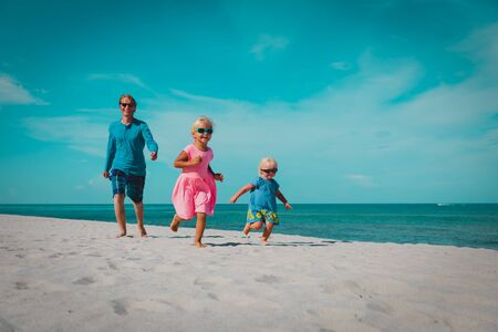 father with little daughters play, run at beach