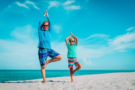 father and son doing yoga at tropical beach
