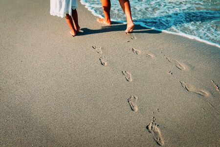 mother and daughter walking on beach leaving footprint in sand Stock Photo - 125871302