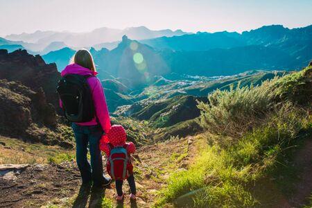 Familia feliz -madre con hija pequeña- viaje en montañas al atardecer