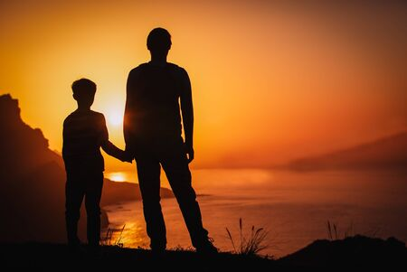 silueta de padre e hijo cogidos de la mano en la naturaleza al atardecer Foto de archivo