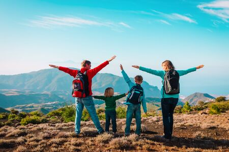 happy mom and dad with kids travel in mountains