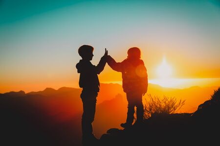 Silhouettes of happy boy and girl hiking at sunset mountains