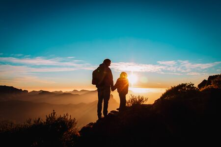 father and daughter travel in mountains at sunset