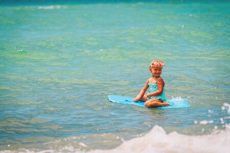 happy little girl play with surf board at sea