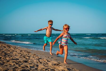 cute happy girl and boy running on beach Foto de archivo