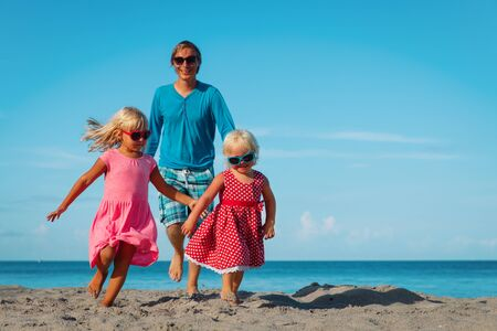 happy family -father with cute little daughters play at beach