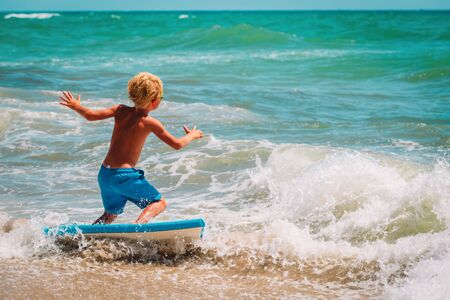 happy boy enjoy surfing at sea, kids play with water on vacaton