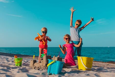 happy kids -boy and girls- play with sand on beach