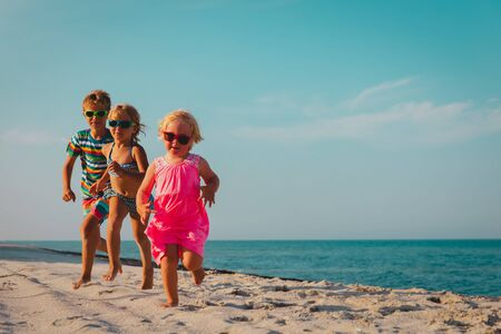 happy kids running on beach, boy and girls have fun at sea