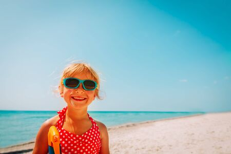 sun protection concept - cute girl with suncream at beach