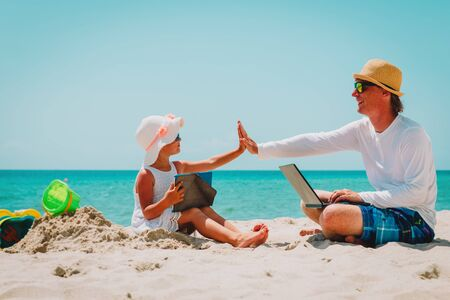 happy father with laptop and cute daughter with touch pad at beach