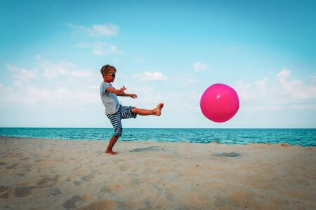 boy play with ball on beach, active games for kids