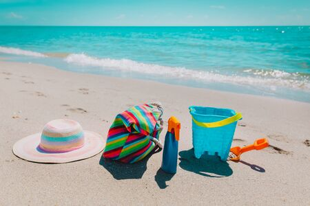 hat, bag ,suncream and toys on beach 写真素材 - 127988843
