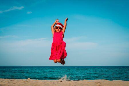 happy little girl enjoy celebrating christmas on tropical beach