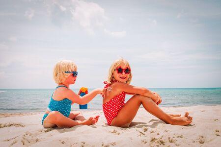sun protection, cute girls with sun cream at beach 版權商用圖片