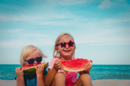 happy cute little girls eating watermelon at beach Stock Photo