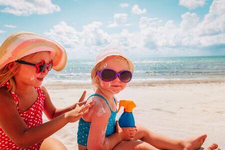 sun protection, cute girls with sun cream at beach Reklamní fotografie
