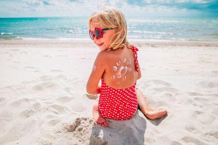 sun protection- happy little girl with suncream at beach Reklamní fotografie