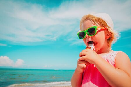 happy cute little girl eating ice cream on beach Banco de Imagens