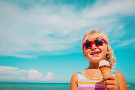 happy cute girl eating ice cream on beach