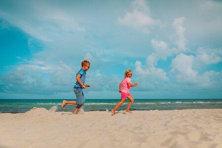 happy boy and girl running on beach Imagens