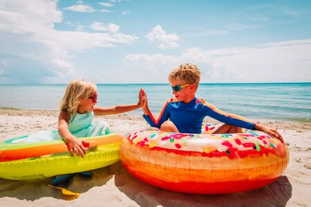 happy cute boy and girl play with floaties on beach