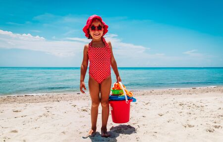 cute little girl playing with sand on the beach Imagens