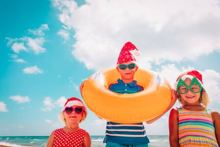 happy kids- boy and girls- celebrating christmas on tropical beach Stock Photo