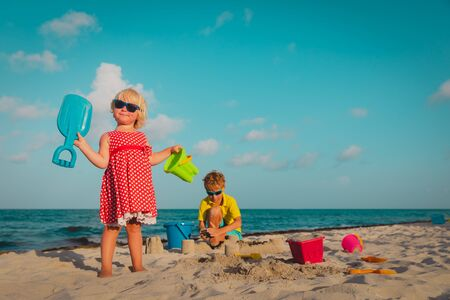 kids play with sand on beach, cute girl and boy building castle