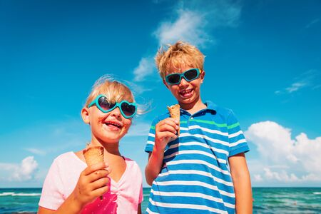 happy kids- boy and girl- eating ice cream on beach Imagens