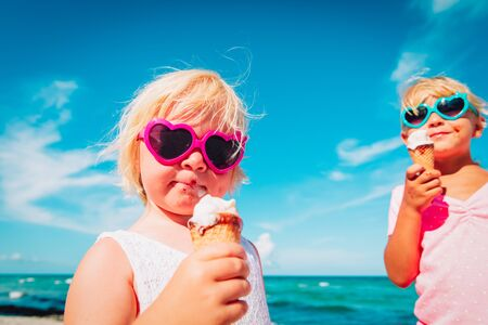 happy cute little girls eating ice cream on beach