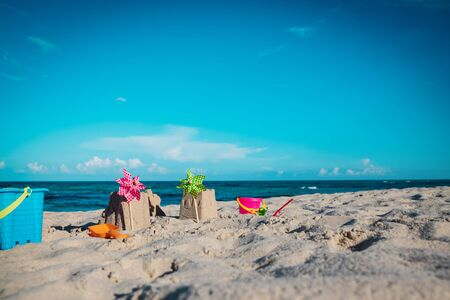 sand toys and castle on tropical beach, kids play on sea vacation