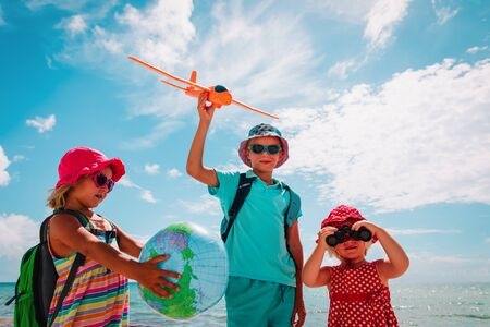 kids travel on beach, boy and girls with globe, toy plane and binoculars at sea