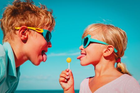 happy little girl and boy with lollipop on summer vacation Imagens
