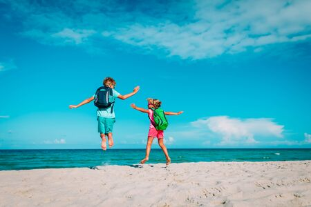 happy kids with backpacks enjoy travel on beach