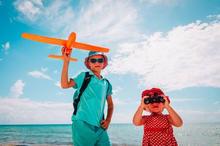 kids travel on beach, boy and girl with toy plane and binoculars at sea