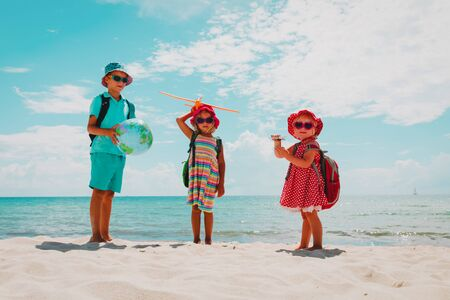 kids travel on beach, boy and girls with globe and toy plane at sea