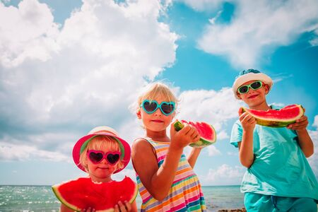 happy cute kids eating watermelon at beach Imagens