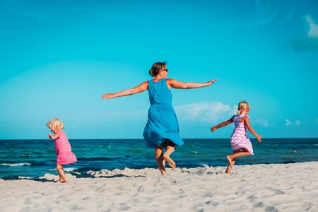 happy mother with little daughters play on beach