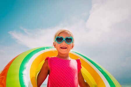 happy cute little girl with floating ring at beach