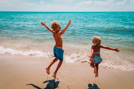 happy cute boy and girl play on beach