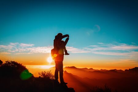 happy father and daughter travel in mountains at sunset Imagens