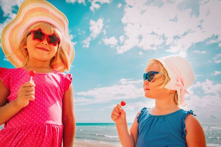 happy cute girls with lollipops on summer vacation Imagens
