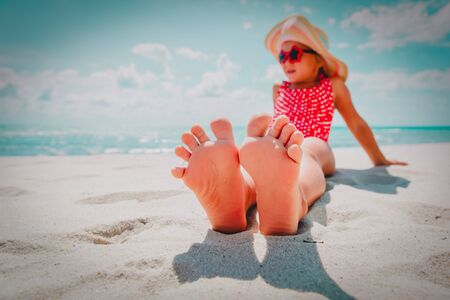 feet of little girl relax at summer beach