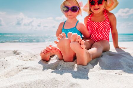 little girls play with sand on beach vacation